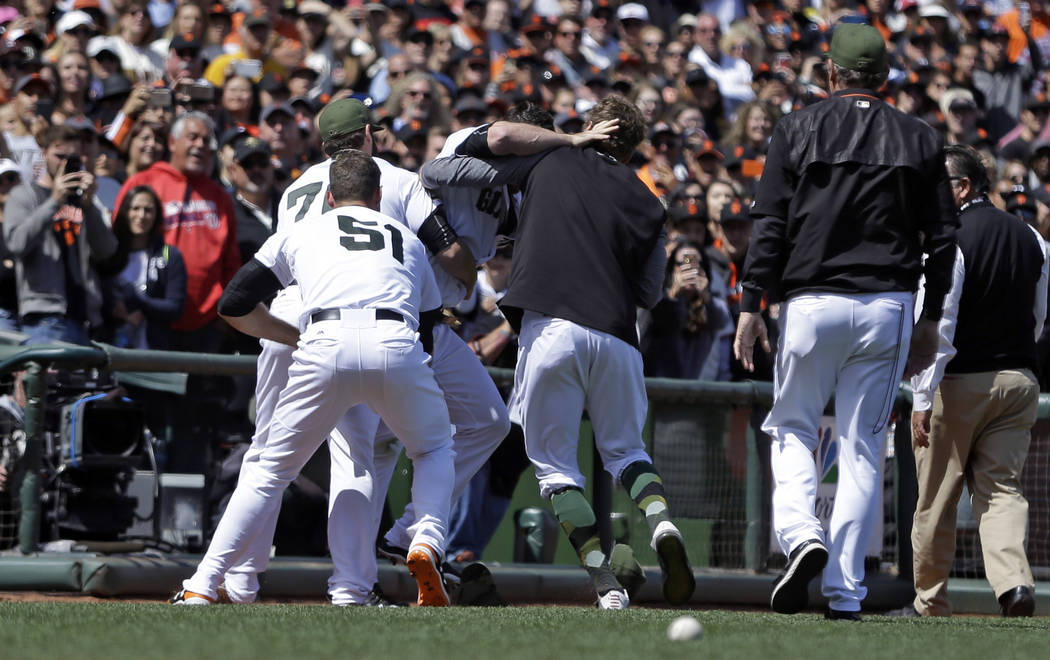 San Francisco Giants including George Kontos (70) and Mac Williamson (51) assist in escorting Hunter Strickland off the field after a brawl with the Washington Nationals in the eighth inning of a  ...