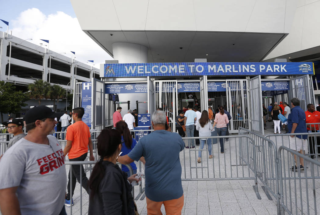 Fans enter Marlins Park stadium before the start of a baseball game between the Miami Marlins and the Atlanta Braves, Tuesday, April 11, 2017, in Miami. (AP Photo/Wilfredo Lee)