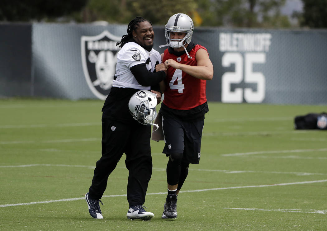 Oakland Raiders running back Marshawn Lynch, left, shakes hands with quarterback Derek Carr during the team's organized team activity at its NFL football training facility Tuesday, May 30, 2017, i ...