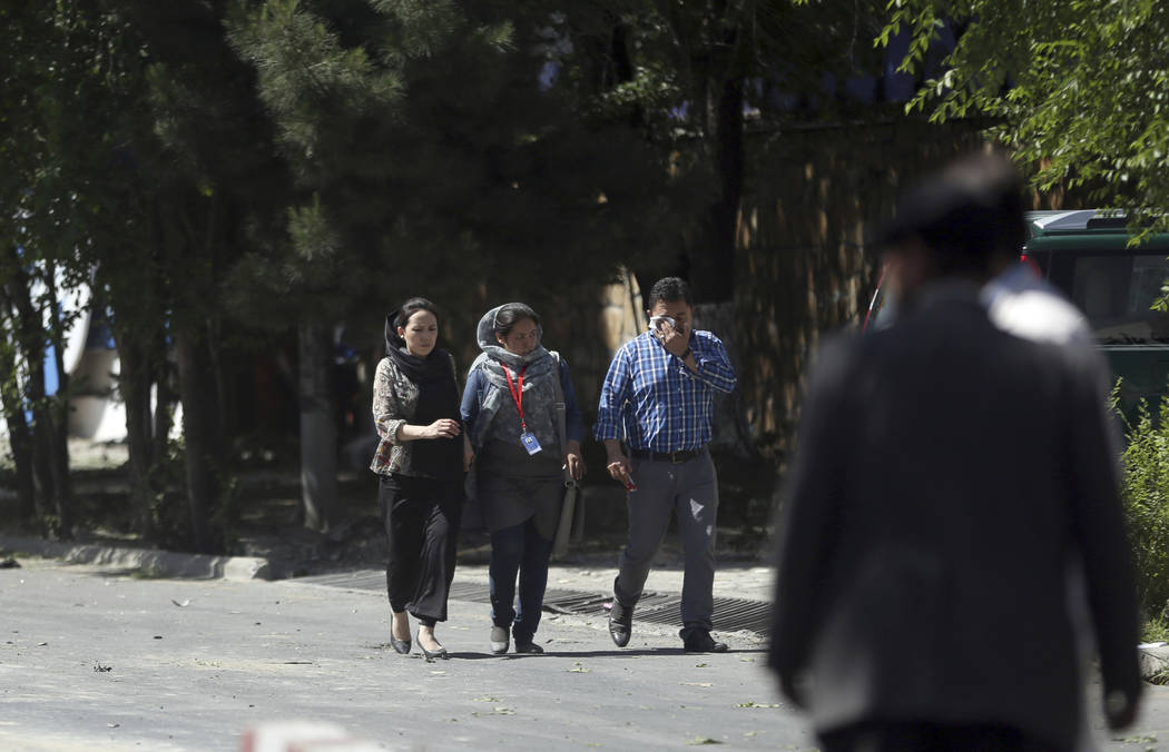Roshan mobile company employees, walk away near the site of a suicide attack in Kabul, Afghanistan, Wednesday, May 31, 2017. A massive explosion rocked a highly secure diplomatic area of Kabul on  ...
