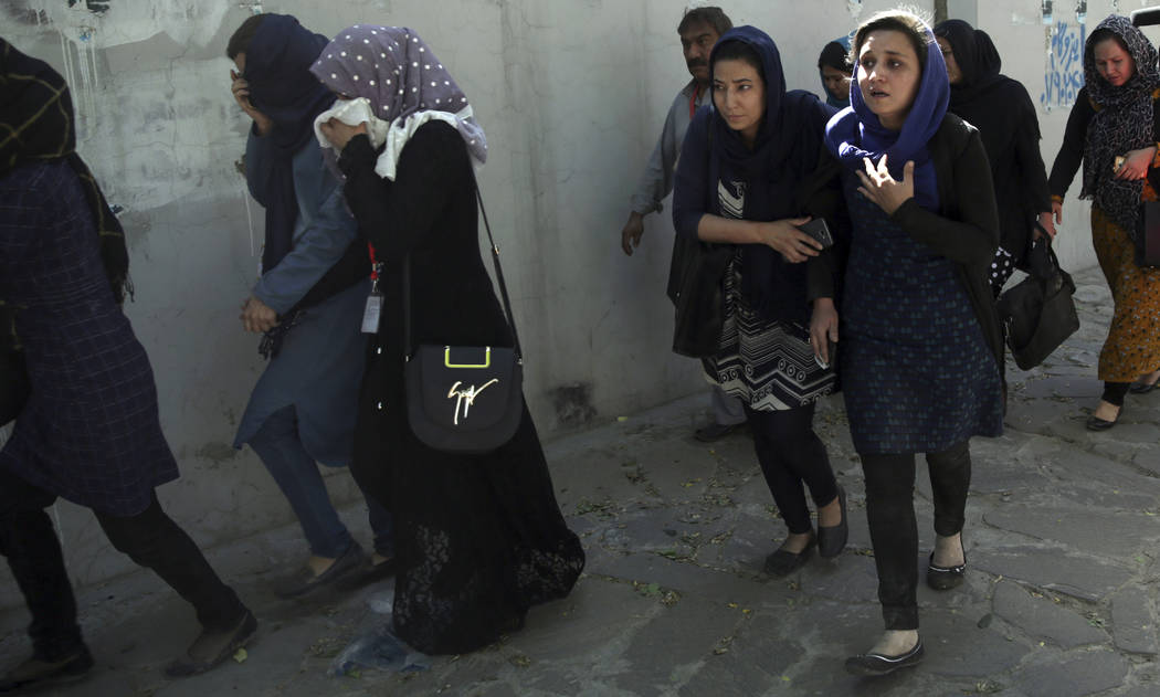 Roshan mobile company employees leave the site of a suicide attack in Kabul, Afghanistan, Wednesday, May 31, 2017. A massive explosion rocked a highly secure diplomatic area of Kabul on Wednesday  ...