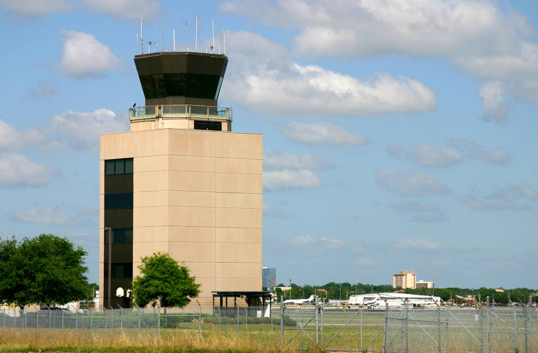 FAA airport control tower, Orlando Executive Airport, Florida. Building is framed against gently clouded blue skies and green grass fields.