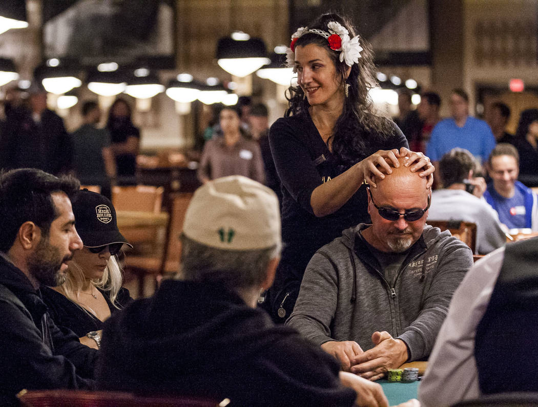 A man gets a massage while playing poker during the opening of the World Series of Poker at the Rio Convention Center on Wednesday, May 31, 2017. Patrick Connolly Las Vegas Review-Journal @PConnPie