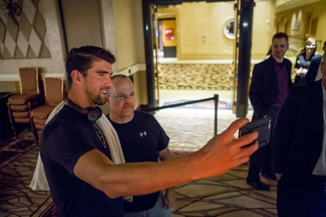 Olympic swimmer Michael Phelps takes a selfie with Adam Maas of Los Angeles before a tag team event in the opening of the World Series of Poker at the Rio Convention Center on Wednesday, May 31, 2 ...