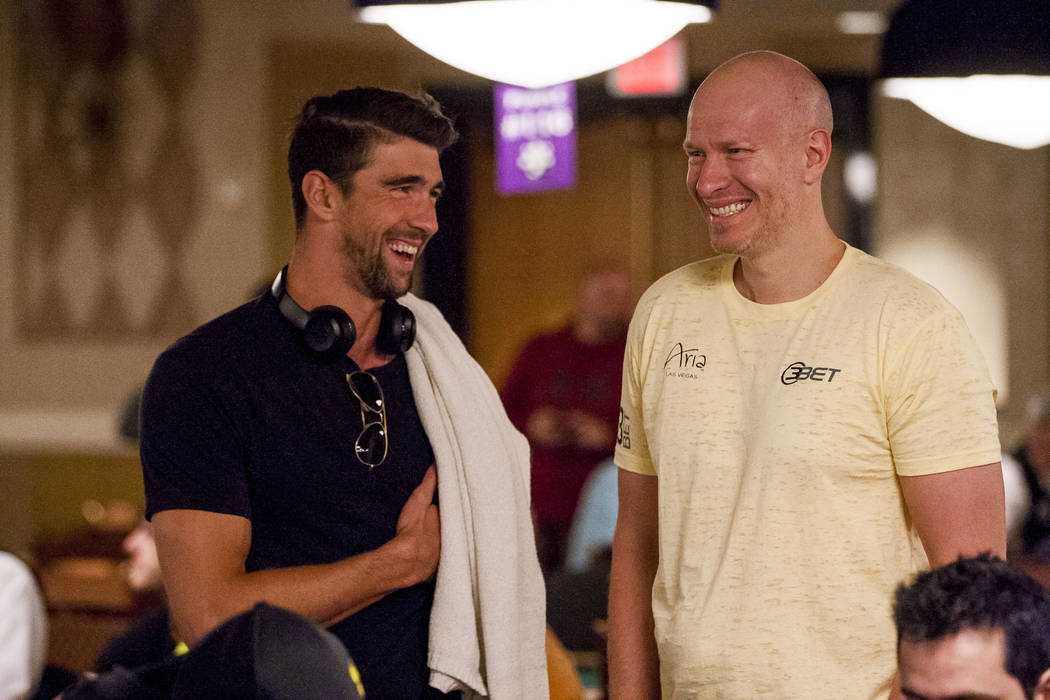 Olympic swimmer Michael Phelps talks with Greg Mueller, a professional poker player and former professional hockey player, before a tag team event in the opening of the World Series of Poker at th ...