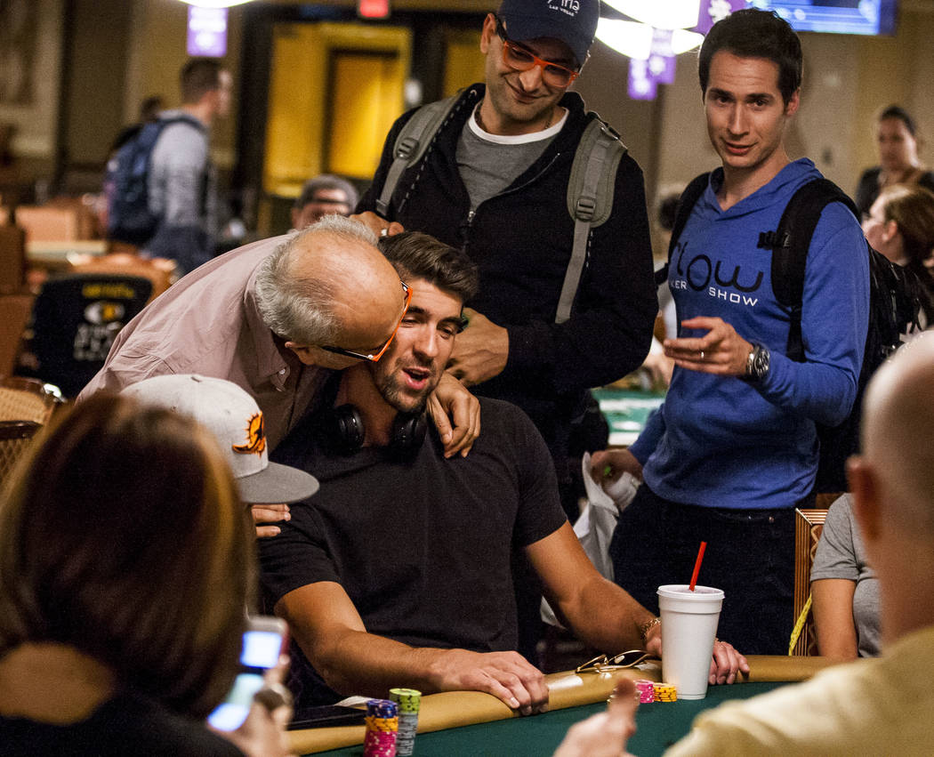 Bejan Esfandiari, father of poker star Antonio Esfandiari, gives Olympic swimmer Michael Phelps plays poker during a tag team event in the opening of the World Series of Poker at the Rio Conventio ...
