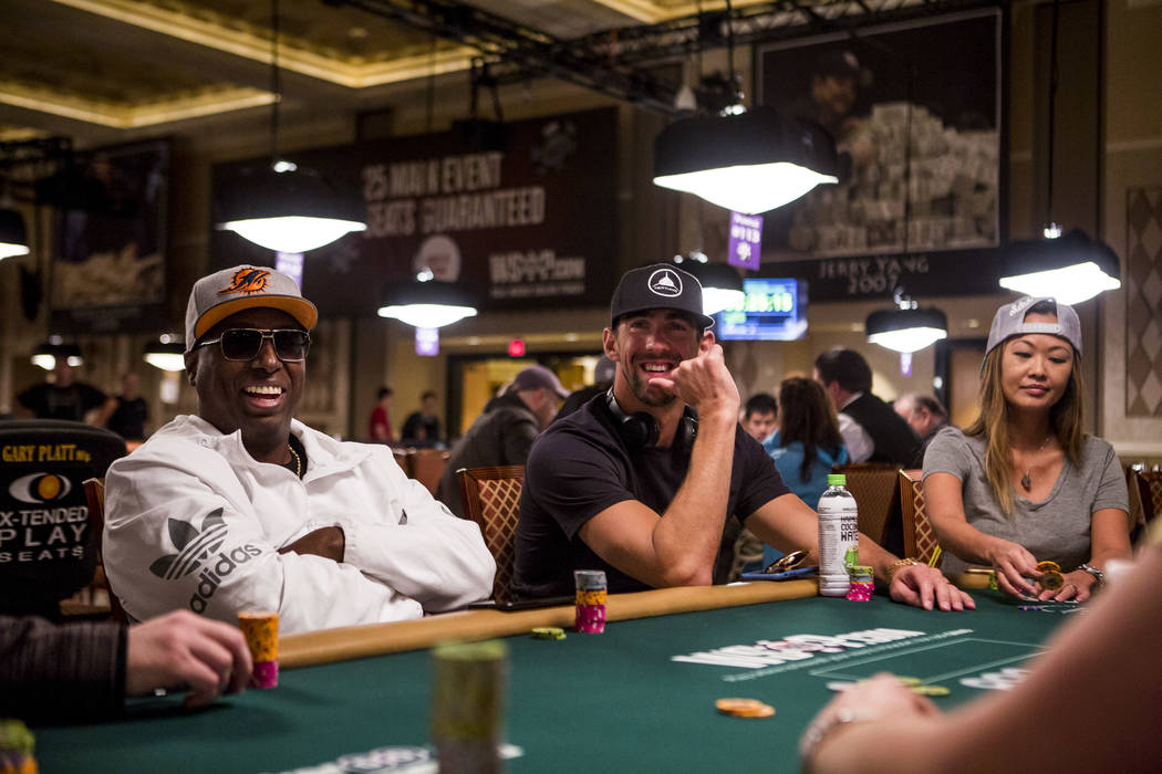 Olympic swimmer Michael Phelps shares a moment with poker star Maurice Hawkins during a tag team event in the opening of the World Series of Poker at the Rio Convention Center on Wednesday, May 31 ...