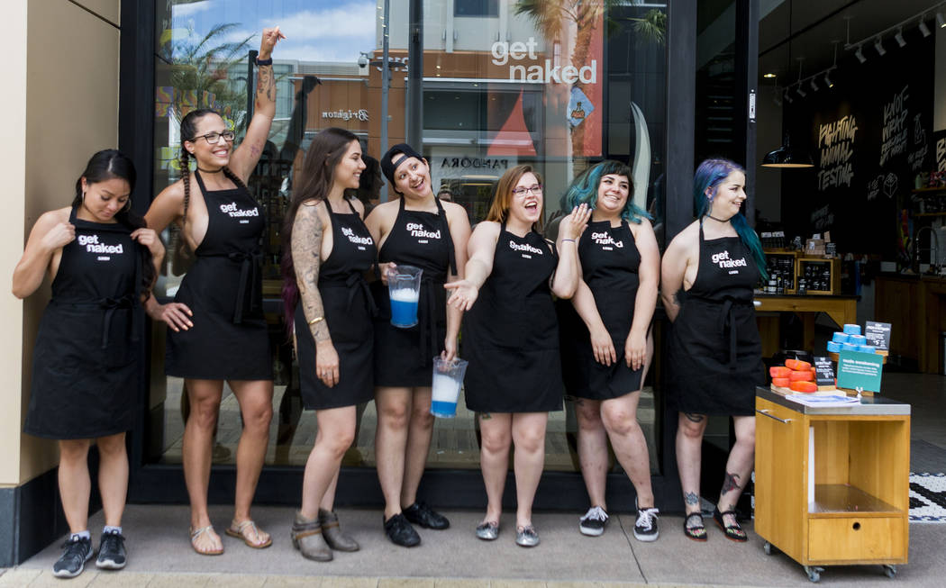"""Lush cosmetic employees stand on the sidewalk of the Downtown Summerlin shopping center only wearing their signature apron to encourage costumers to buy their environmentally friendly """"na ..."""