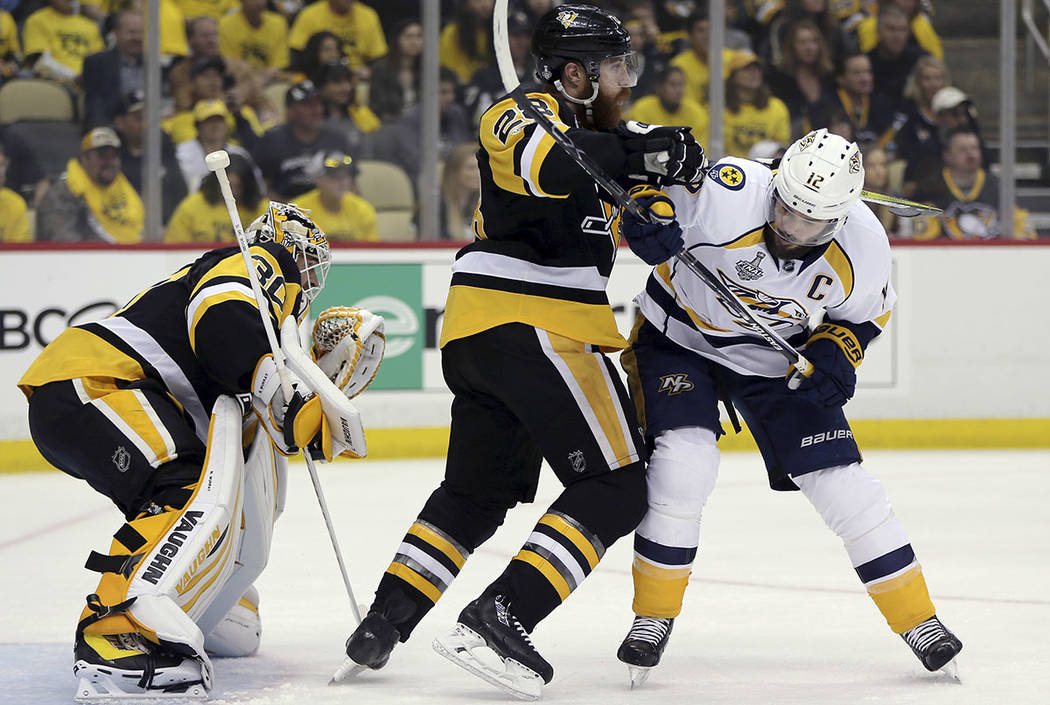 Pittsburgh Penguins' Ian Cole, center, checks Nashville Predators' Mike Fisher (12) in front of Penguins goalie Matt Murray (30) during the first period in Game 2 of the NHL hockey Stanley Cup Fin ...