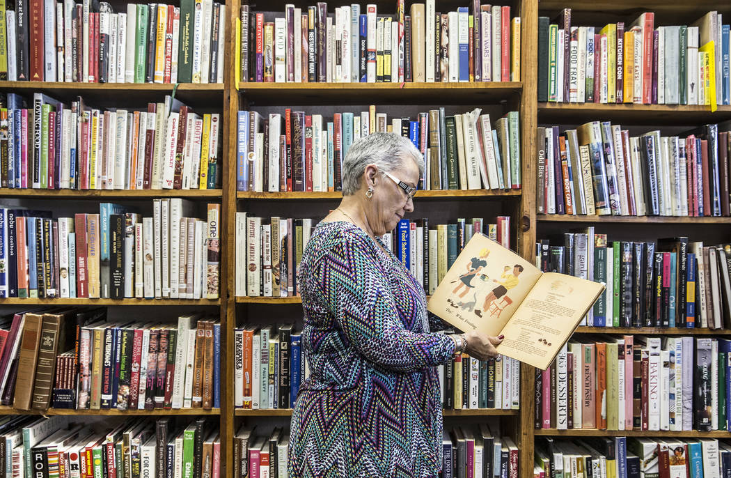 Amber Unicorn Books owner Myrna Donato looks through one of thousands of cookbooks she's collected over the past 35 years. Photo taken on Monday, March 20, 2017, at Amber Unicorn Books, in Las Veg ...