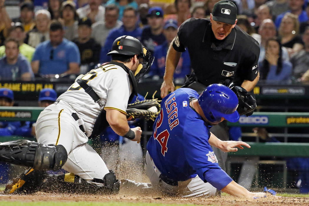 Pittsburgh Pirates catcher Francisco Cervelli, left, tags out Chicago Cubs' Jon Lester (34) show as attempting to score on a fielder's choice by Cub's Kyle Schwarber to Pirates' first baseman Josh ...