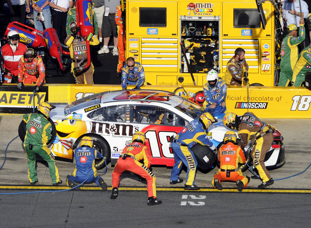 Crew members perform a pit stop on Kyle Busch's car during the NASCAR Cup series auto race at Charlotte Motor Speedway in Concord, N.C., Sunday, May 28, 2017. (AP Photo/Mike McCarn)