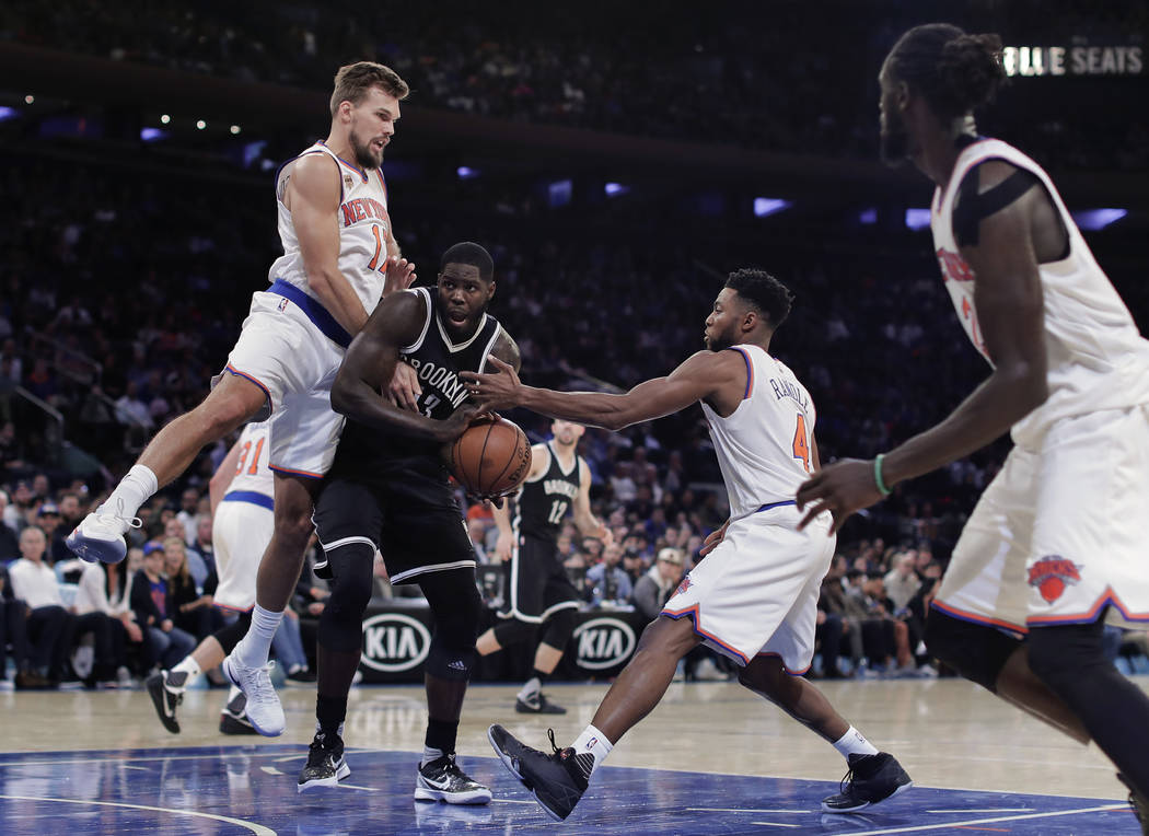 Brooklyn Nets forward Anthony Bennett, center, tries to drive between New York Knicks forward Lou Amundson, left, and guard Chasson Randle (4) during the fourth quarter of a preseason NBA basketba ...