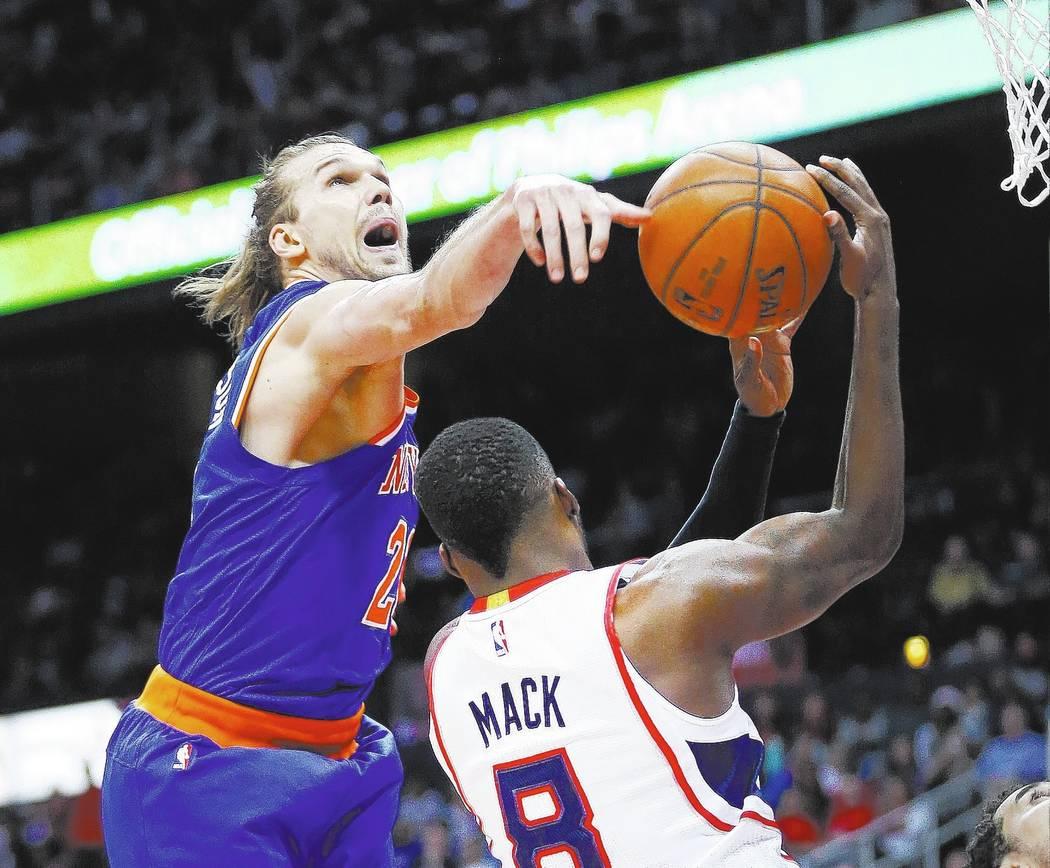 Atlanta Hawks guard Shelvin Mack (8) has his shot blocked by New York Knicks forward Lou Amundson (21) during the first half of an NBA basketball game Monday, April 13, 2015, in Atlanta. (AP Photo ...