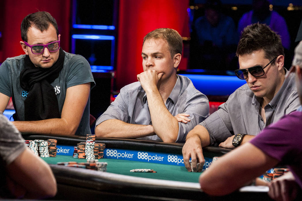 Rainer Kempe, left, Andrew Robl, center, and Doug Polk, right, compete in the World Series of Poker's $111,111 buy-in High Roller for One Drop No-limit Hold'em tournament at the Rio Convention ...