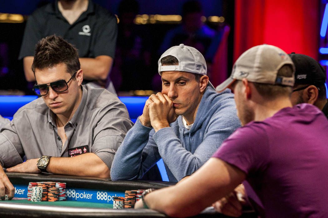 Haralabos Voulgaris, center, and Doug Polk, left, compete in the World Series of Poker's $111,111 buy-in High Roller for One Drop No-limit Hold'em tournament at the Rio Convention Center on Mo ...
