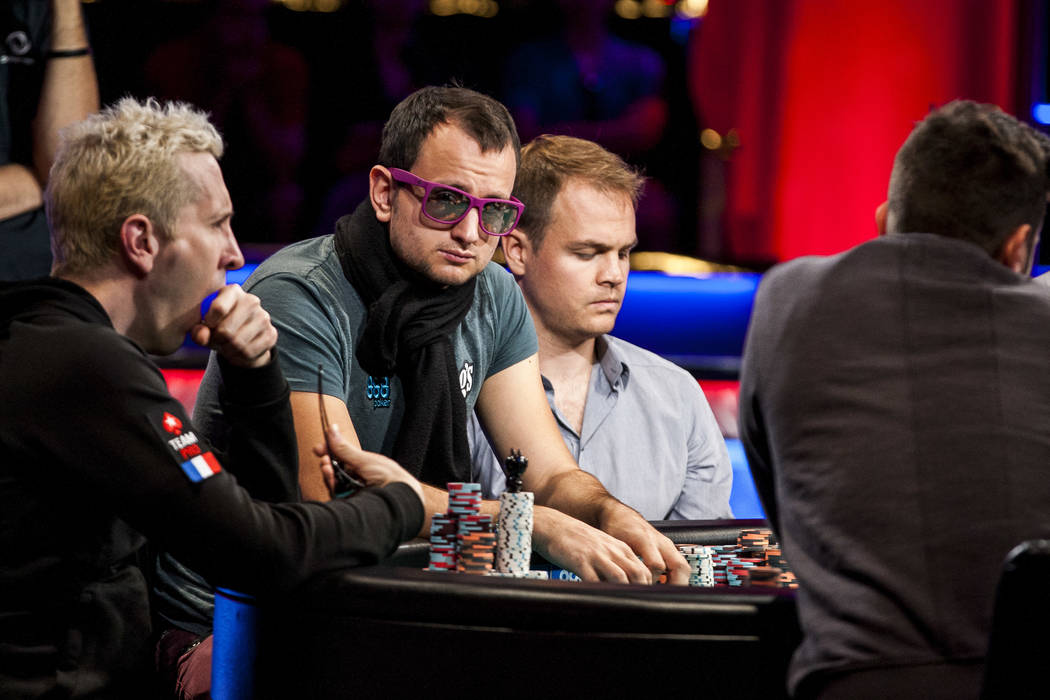 Players including Rainer Kempe, center, compete in the World Series of Poker's $111,111 buy-in High Roller for One Drop No-limit Hold'em tournament at the Rio Convention Center on Monday, June ...