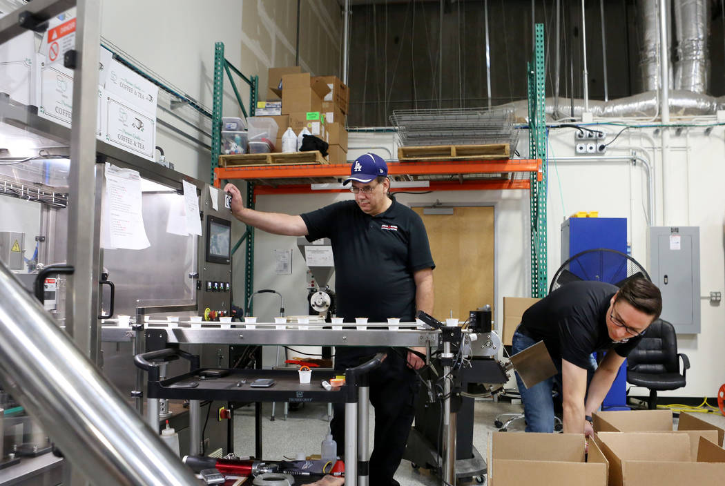 Operation Manager for Stella Brands Packing and Printing Jim Chestnut, left, and owner Brent Patterson, produce single serve coffee cups at the company warehouse in Las Vegas, Tuesday,  May 30, 20 ...