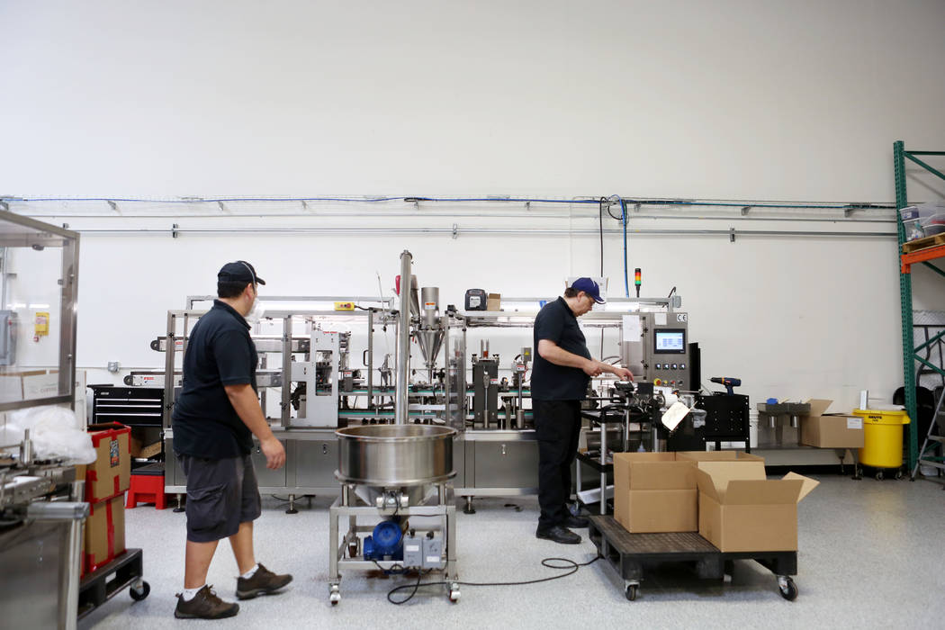 Operator Ramon Castro, left, and operation manager for Stella Brands Packing and Printing Jim Chestnut produce single serve coffee cups at the company warehouse in Las Vegas, Tuesday,  May 30, 201 ...