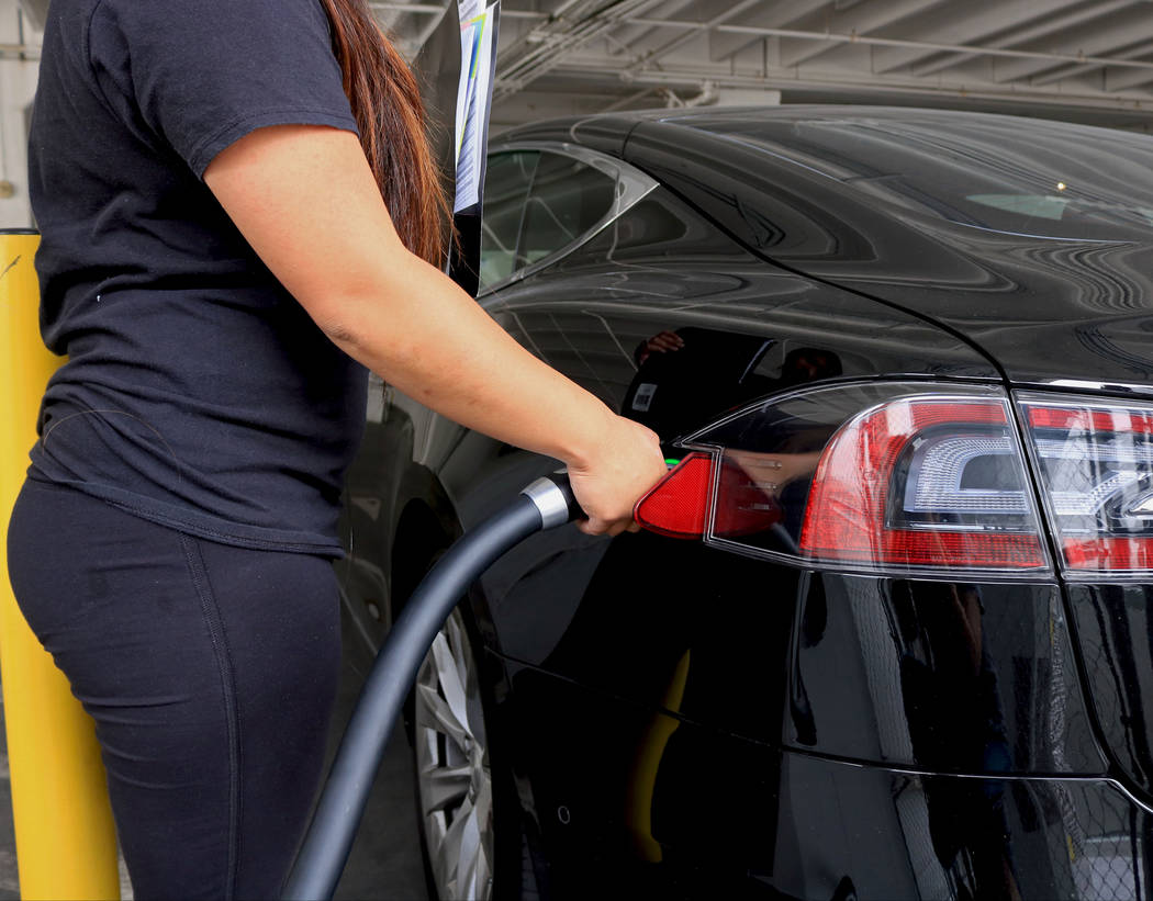 A woman charges her car at an EV charging station on East Bridger Avenue, Wednesday, May 31, 2017. Gabriella Benavidez Las Vegas Review-Journal @latina_ish