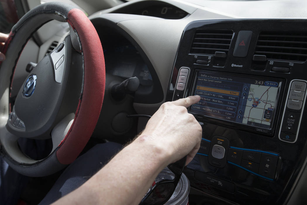 Lloyd Reece, president of the Las Vegas Electric Vehicle Association, points to a map displaying charging stations in the area while driving his 2011 Nissan Leaf in Las Vegas on Wednesday, May 31, ...