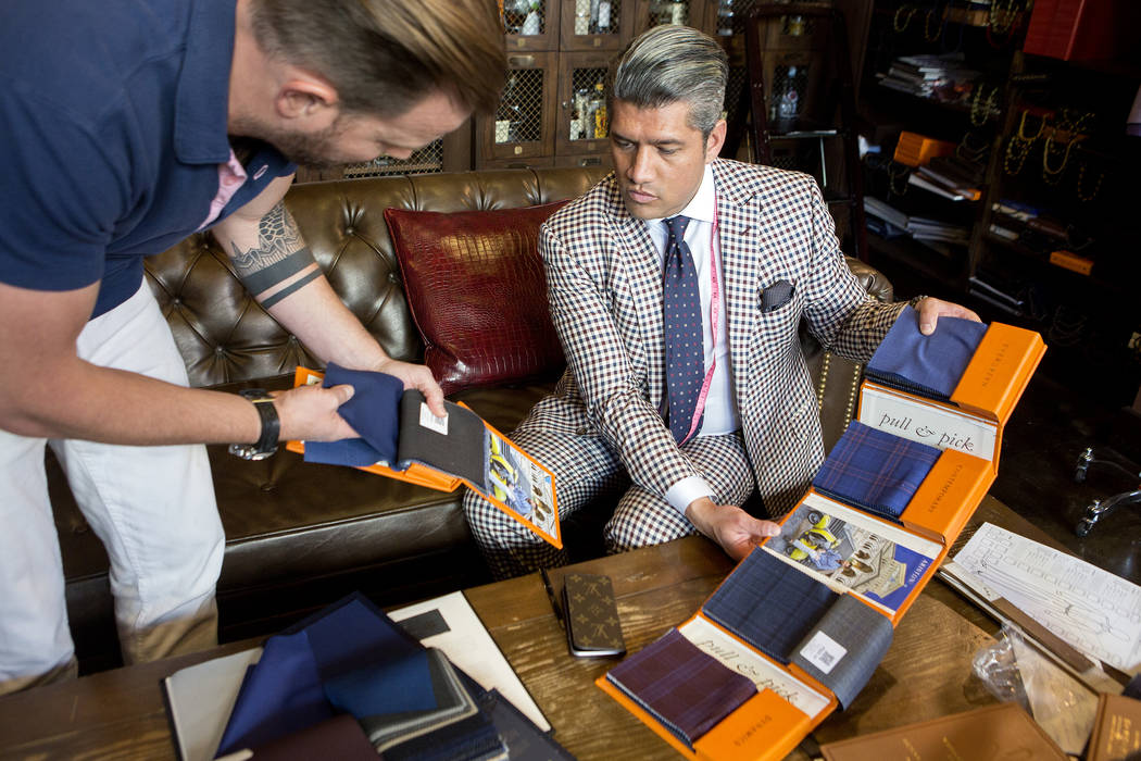 Stitched General Manager Ricci Lopez, right, works with customer Matt Welebir to choose fabric for a custom tuxedo for his wedding. Though a Stitched custom suit costs $1,800 on average, fabric qu ...