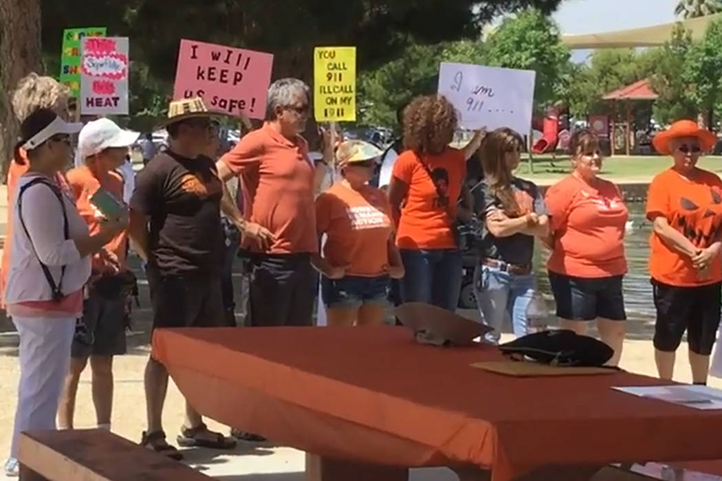 Volunteers with Moms Demand Action stand in front of counter-protesters on June 3, 2017, as a speaker reads a declaration acknowledging Wear Orange Day from Henderson Mayor Andy Hafen. (Katelyn Ne ...