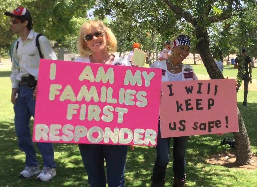 Two counter-protesters stand with signs advocating for gun ownership on June 3, 2017, during Wear Orange Day. The event, organized by Moms Demand Action, was for volunteers to advocate for gun saf ...