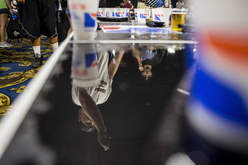 Casey Costa of New Jersey is reflected in a table as he attempts a shot during the World Series of Beer Pong at the Westgate Las Vegas on Sunday, June 4, 2017. Patrick Connolly Las Vegas Review-Jo ...