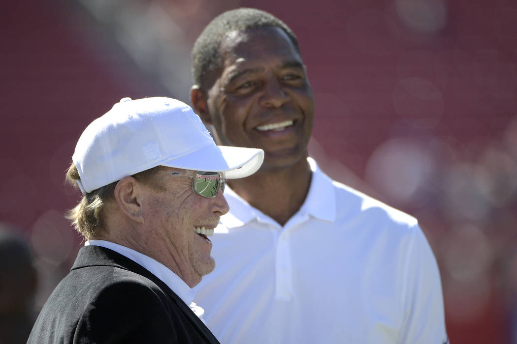 Oakland Raiders owner Mark Davis, left, and former Raiders running back Marcus Allen share a laugh while watching warmups before an NFL football game against the Tampa Bay Buccaneers in Tampa, Fla ...