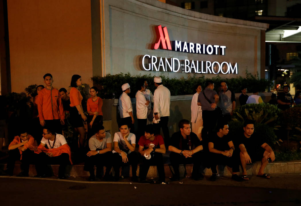 Evacuated employees are seen at the entrance of a hotel near a situation at a Resorts World building in Pasay City, Metro Manila, Philippines June 2, 2017. (Erik De Castro/Reuters)
