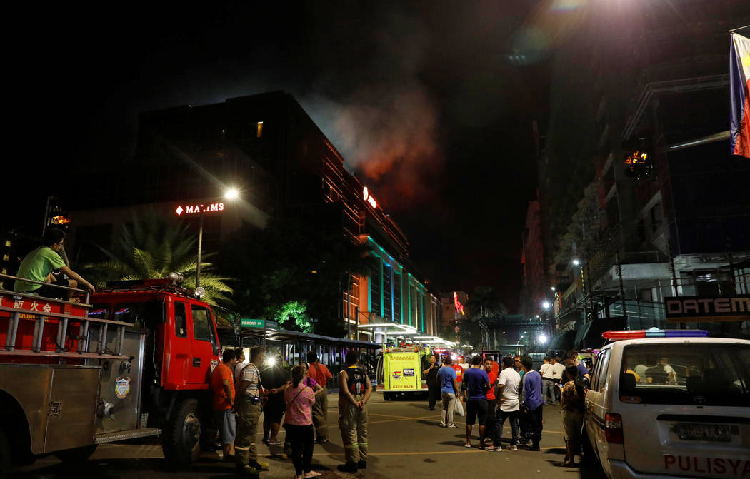Evacuated employees and guests of hotels stand along a road and watch as smoke billows from a Resorts World building in Pasay City, Metro Manila, Philippines June 2, 2017. (Erik De Castro/Reuters)