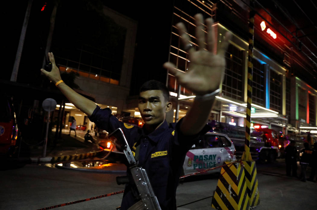 A security guard stops photographers from entering the vicinity of Resorts World Manila after gunshots and explosions were heard in Pasay City, Metro Manila, Philippines June 2, 2017. (Erik De Cas ...
