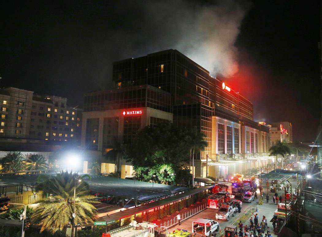 Smoke rises from the Resorts World Manila complex early Friday, June 2, 2017 in suburban Pasay city southeast of Manila, Philippines. Friday, June 2, 2017. Gunshots and explosions rang out early F ...