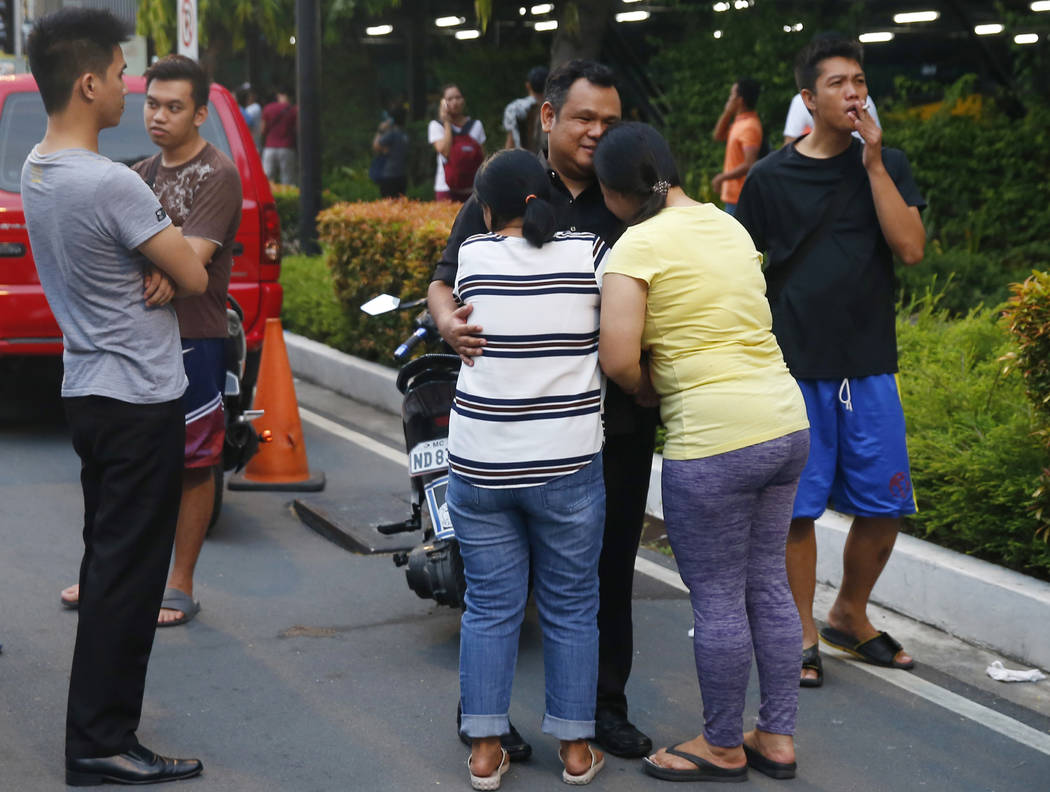 Relatives react after finding a casino employee, center, safe at the Resorts World Manila complex in suburban Pasay city, southeast of Manila, Philippines Friday, June 2, 2017. A gunman stormed a  ...