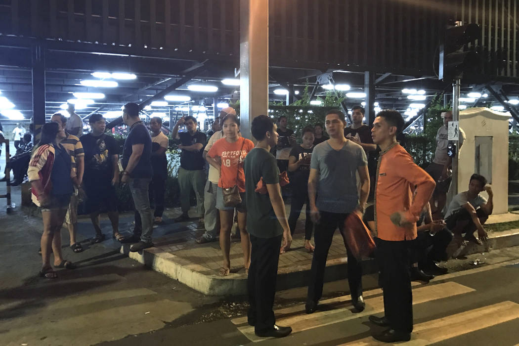 Employees and onlookers gather outside the Resorts World Manila complex, early Friday, June 2, 2017, in Manila, Philippines. Gunshots and explosions rang out early Friday at a mall, casino and hot ...