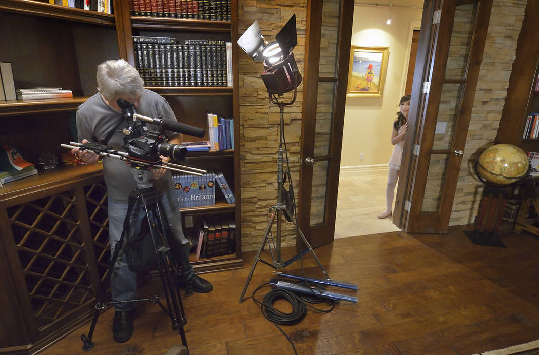 Director of photography Don Starnes frames a shot as actress Grace O'Shaughnessy waits to make her entrance during the making of a video to be used as a sales tool for a luxury home in the  ...