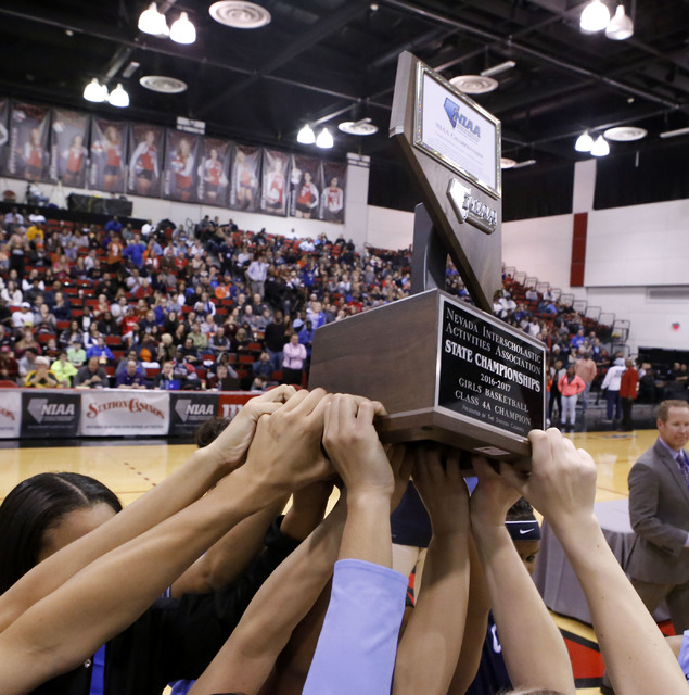 Centennial players thrusts their trophy into the air after winning their third straight Class 4A girls state final championship game at the Cox Pavillion on Friday, Feb. 24, 2017, in Las Vegas. Ce ...