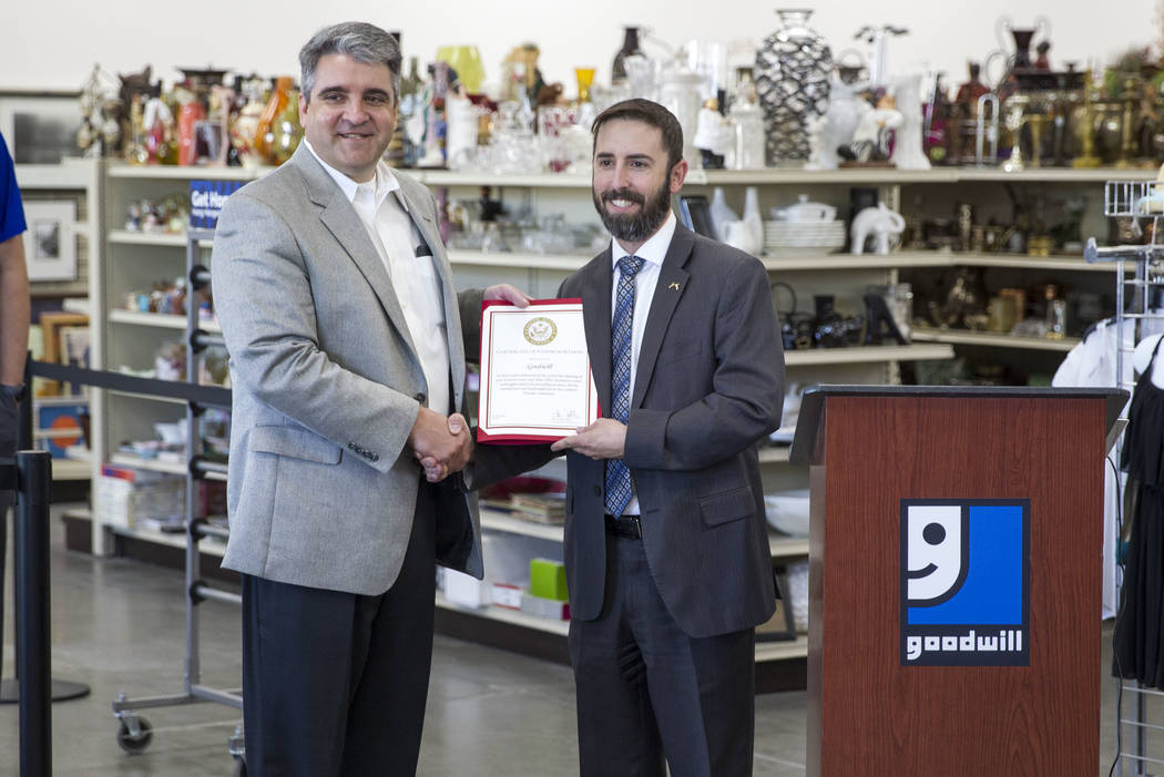 Interim Goodwill of Southern Nevada CEO John Helderman, left, is presented with a certificate of commemoration by Senator Dean Heller representative Bradley Sensibaugh during a reopening event for ...