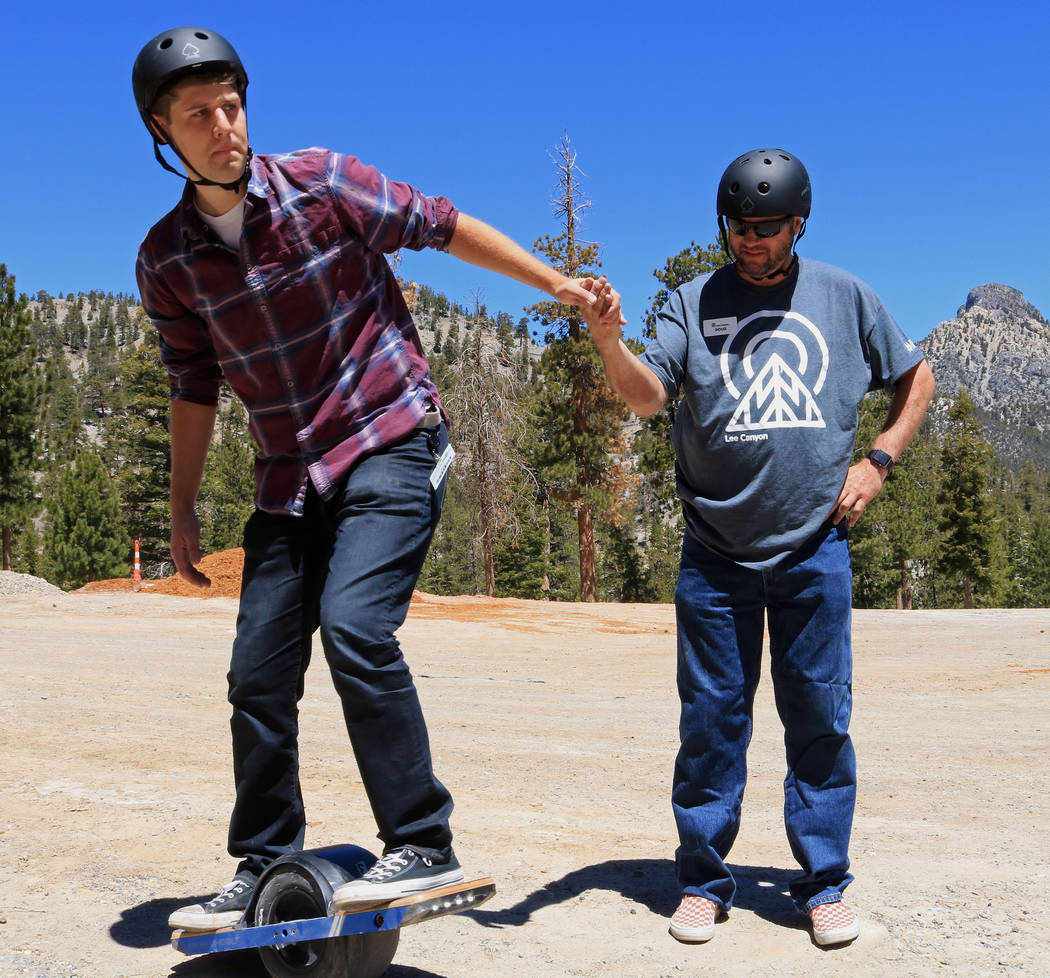 Las Vegas Review-Journal reporter Ben Gotz, left, is assisted by Doug Benson while trying out a Onewheel, an electrical self-balancing skateboard at Lee Canyon, Friday, May 26, 2017. Gabriella Ben ...