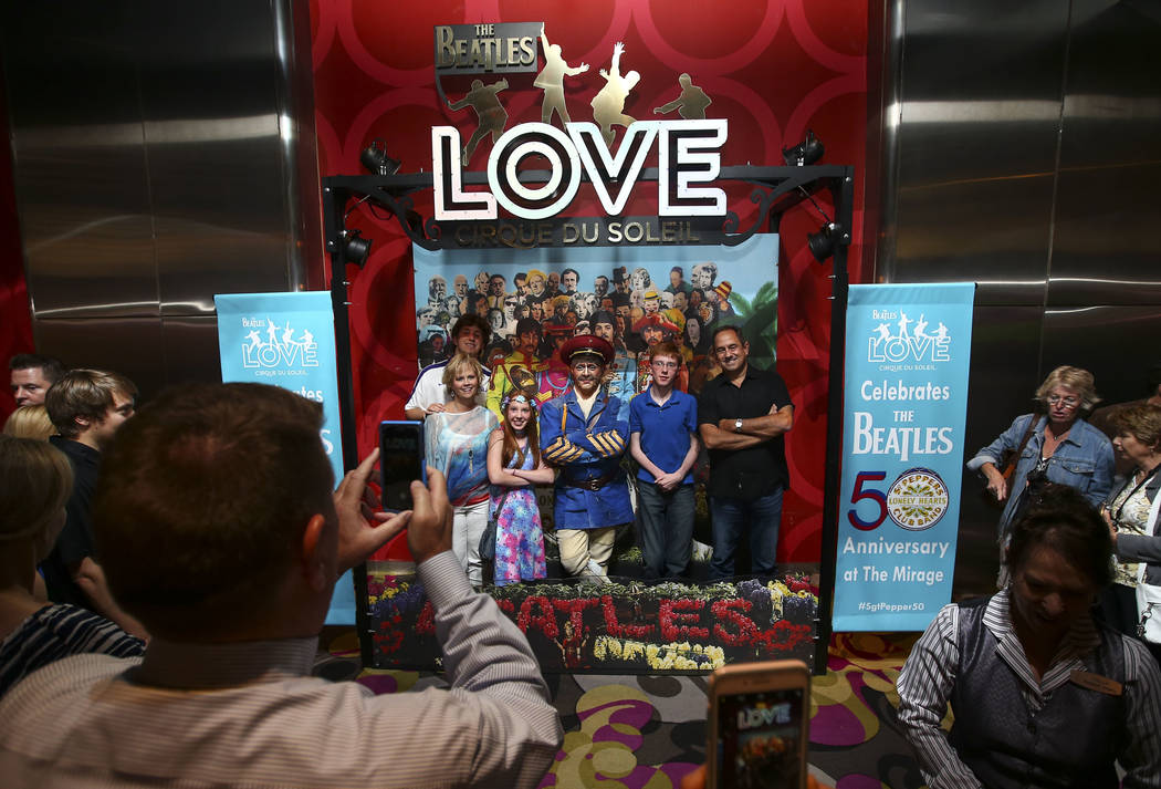 "Vladimir Sosnine, who plays ""Sgt. Pepper"" in Cirque du Soleil's ""The Beatles LOVE,"" poses for photos with people following a performance by a display commemorating the 50th anniversary of the The  ..."