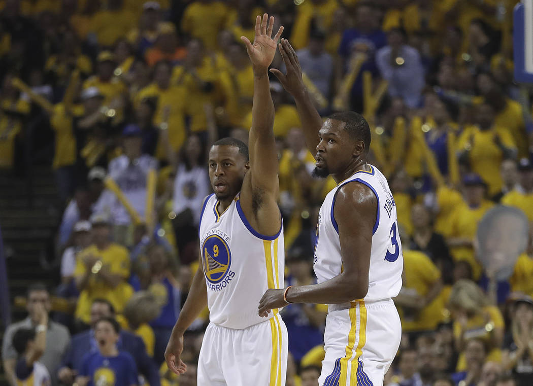 Golden State Warriors forward Andre Iguodala (9) and forward Kevin Durant (35) react after scoring against the Cleveland Cavaliers during the first half of Game 1 of basketball's NBA Finals in Oak ...