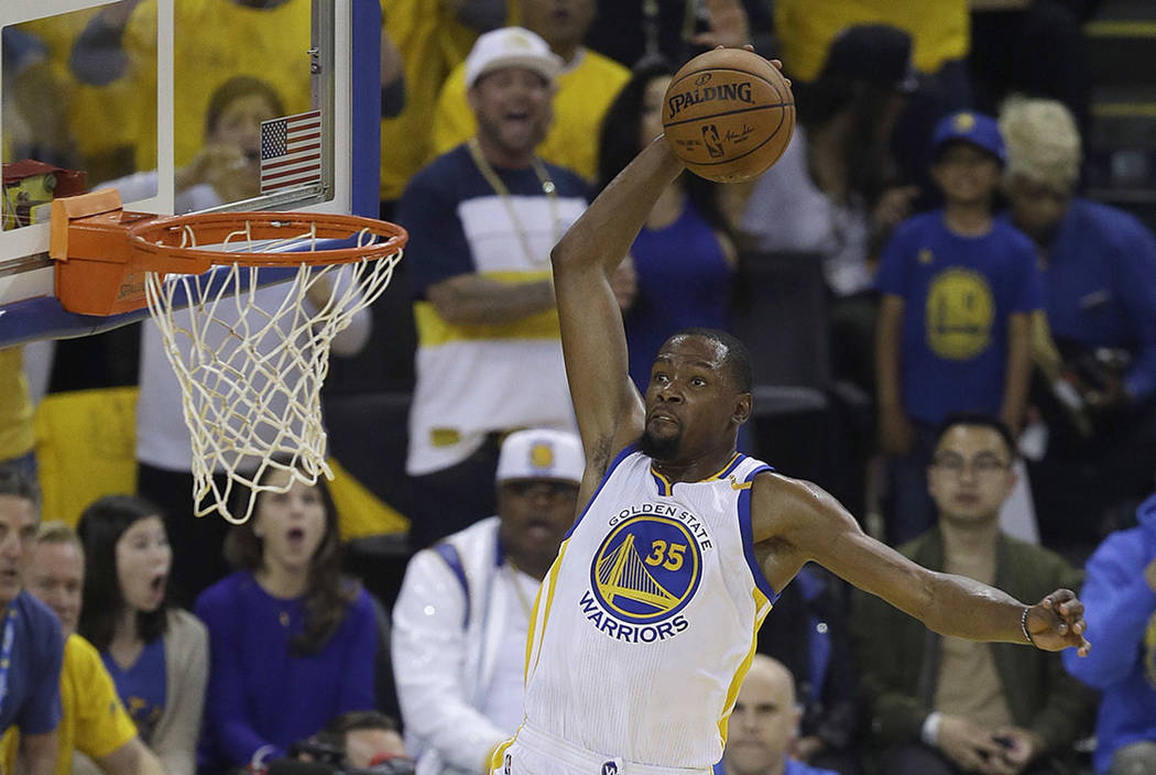 Golden State Warriors forward Kevin Durant (35) dunks against the Cleveland Cavaliers during the first half of Game 1 of basketball's NBA Finals in Oakland, Calif., Thursday, June 1, 2017. (AP Pho ...