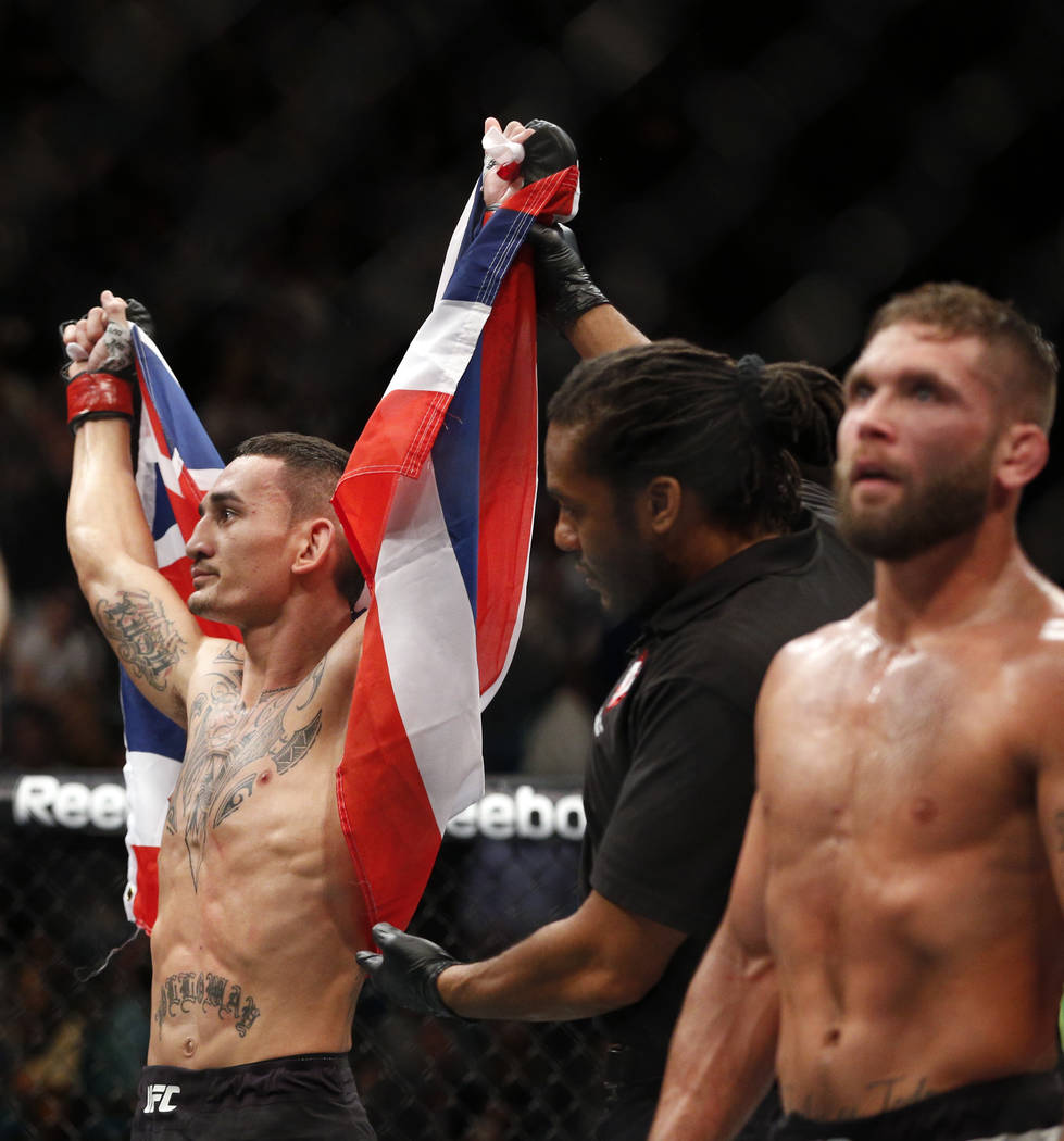 Max Holloway, left, celebrates after defeating Jeremy Stephens, right, in a featherweight mixed martial arts bout at UFC 194, Saturday, Dec. 12, 2015, in Las Vegas. (AP Photo/John Locher)