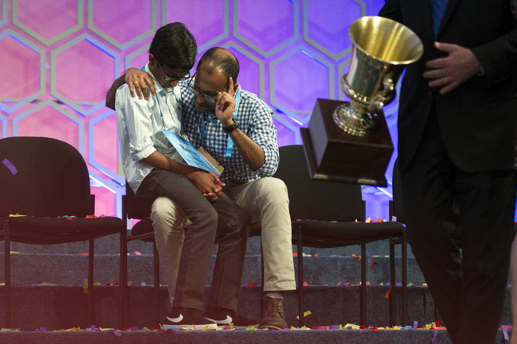 With the winners trophy passing by, Rohan Rajeev, 14, from Edmond, Okla., talks with his father Rajeev Muralidharan, moments after losing in the finals of the 90th Scripps National Spelling Bee in ...