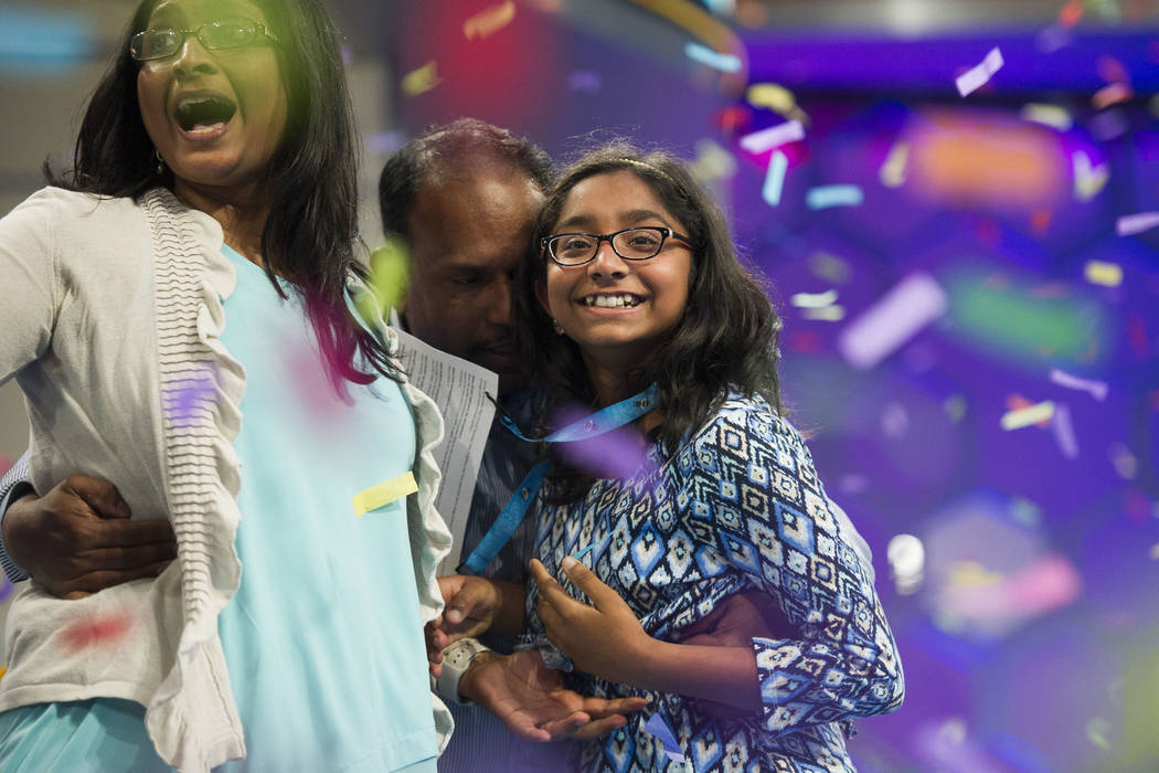 Ananya Vinay, 12, from Fresno, Calif., celebrates onstage with her parents, Anu Pama Poliyedathpp, left, and Vinay Sreekumar, center, after winning the 90th Scripps National Spelling Bee in Oxon H ...