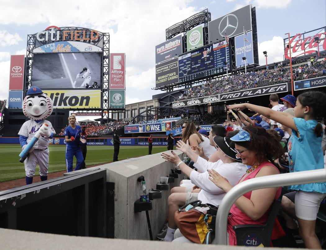 Mr Met, left, distributes t-shirts to fans during the sixth inning of a baseball game against the Milwaukee Brewers Thursday, June 1, 2017, in New York. (AP Photo/Frank Franklin II)