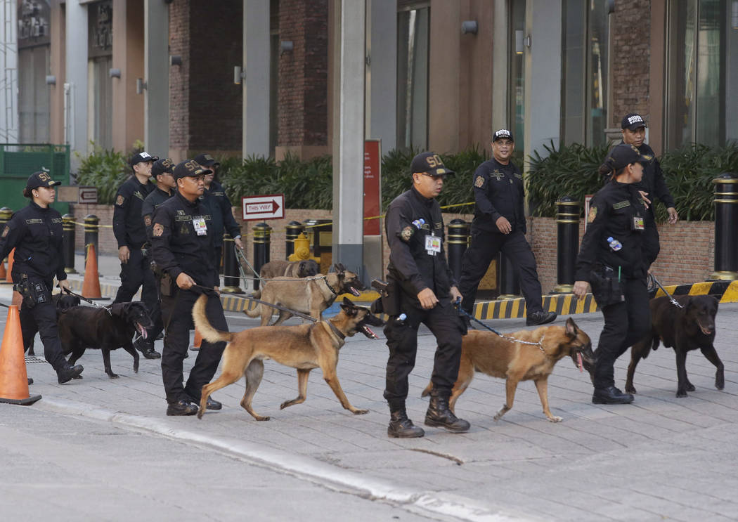 Bomb sniffing dogs walk outside a hotel at the Resorts World Manila complex, early Friday, June 2, 2017, in Manila, Philippines. A gunman stormed a mall-casino complex, torched gambling tables and ...