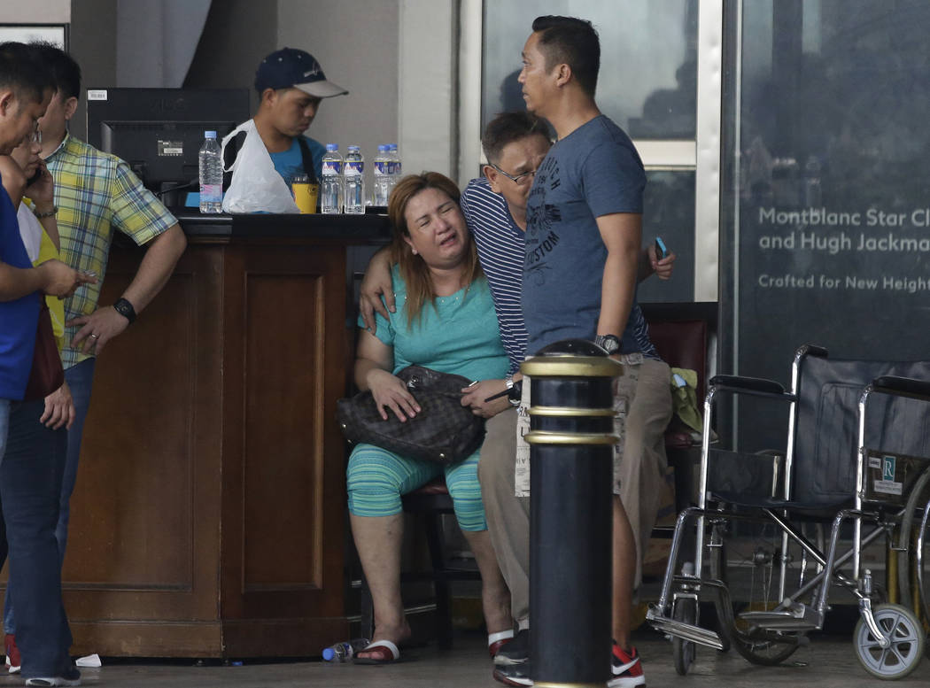 A woman cries as she stay outside a hotel at the Resorts World Manila complex, early Friday, June 2, 2017, in Manila, Philippines. A masked gunman stormed a hotel-casino complex in the Philippine  ...