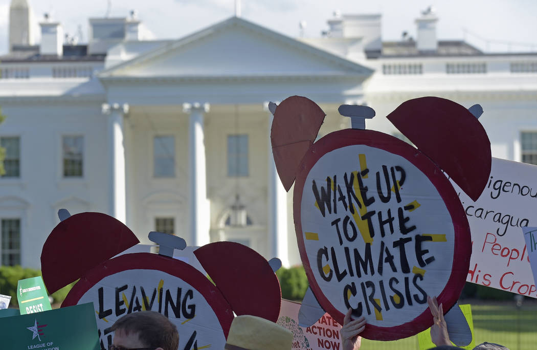 Protesters gather outside the White House in Washington, Thursday, June 1, 2017, to protest President Donald Trump's decision to withdraw the Unites States from the Paris climate change accord. (A ...